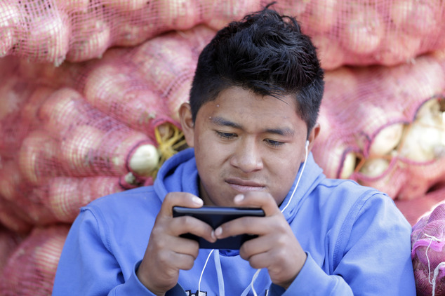 In this Aug. 24, 2014, photo, a young man texts a message on his mobile phone while working at the Mayorista Market in Quito, Ecuador. Ecuador's Central Bank...