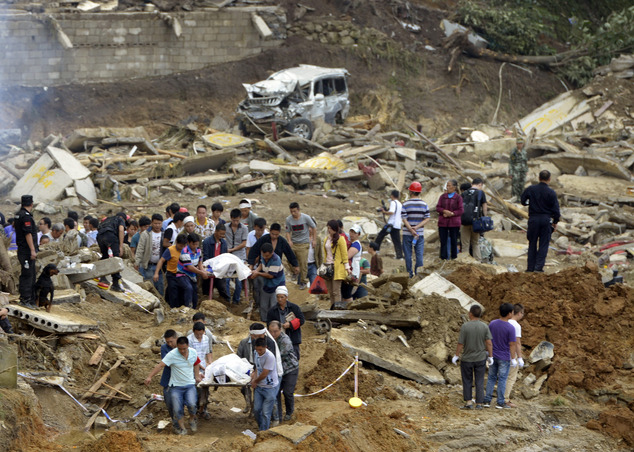 In this Thursday Aug. 28, 2014 photo, residents remove bodies in the aftermath of a landslide at Yingping village in Fuquan city in southwest China's Guizhou...