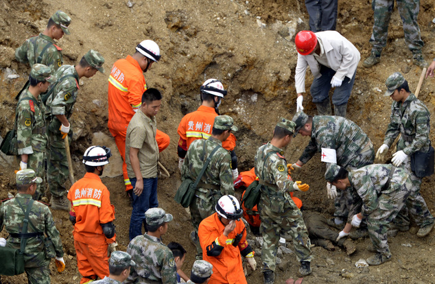 In this Thursday Aug. 28, 2014, rescue workers recover a body in the  aftermath of a landslide at Yingping village in Fuquan city in southwest China's Guizho...