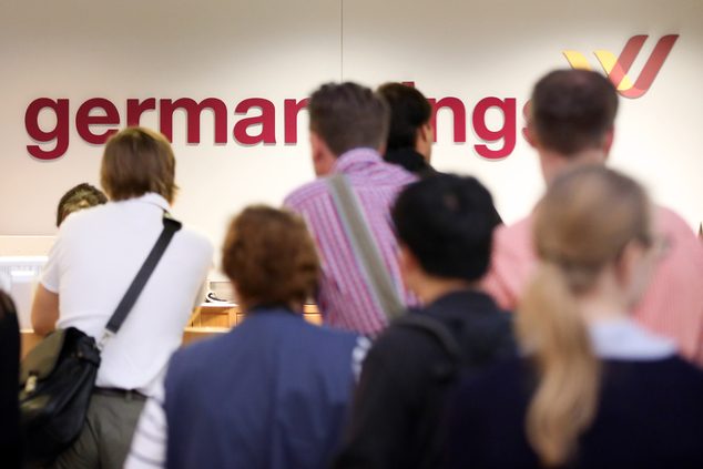 Passenger queue at a desk of German carrier Germanwings at the airport in Hamburg, northern Germany, Friday, Aug. 29, 2014. Thousands of passengers are feeli...