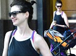Getting clucky? Anne Hathaway smiles adoringly at a passing pram as she heads to the New York set of The Intern in colourful gym clothes