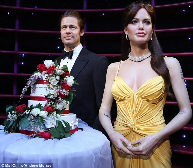 Blood red roses: The couple stand in front of a faux, three-tier cake decorated in a gaudy flower arrangement