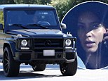 Make-up free Kim Kardashian indulges her sweet tooth with a lollipop while driving her Mercedes SUV