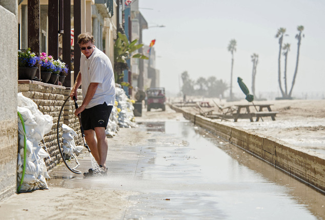 John Breiding washes sand from the boardwalk in front of his beachfront home as huge swells from Hurricane Marie in the Pacific Ocean west of Mexico caused u...