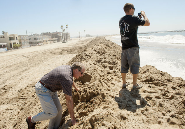 Barry Dahlen, left, of Huntington Beach, Calif. climbs the sand berm in Seal Beach as Dennis Roudabush of Seal Beach videotapes water inundating the beach on...