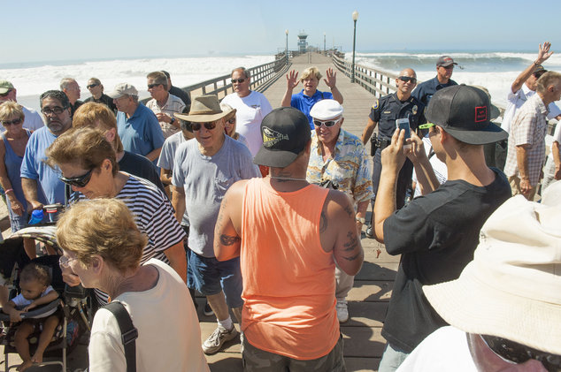 Authorities evacuate spectators from the Seal Beach Pier as huge swells from Hurricane Marie in the Pacific Ocean west of Mexico caused unexpected flooding a...