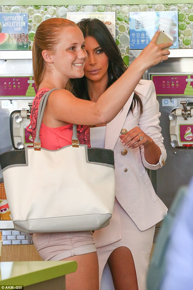 Selfie obsessed: Kim happily posed for a snap with a fan and pulled her signature pout
