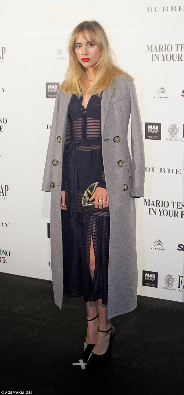 The big cover-up: The model initially arrived at the bash in a long, grey coat, giving only a hint of her dress