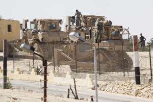 A picture taken from the southern Gaza Strip shows Egyptian soldiers standing on bulldozers used to flatten fields near the border between Egypt and the Palestinian territory (AFP Photo)