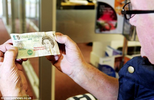 A shop customer pictured with one of the stamped bank notes which have angered locals