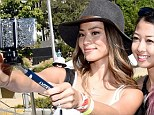 'Cheese!' A playful Jamie Chung uses extra long mono-pods to take selfies with fans while whooping it up at the Budweiser MIA Labour Day party in Los Angeles