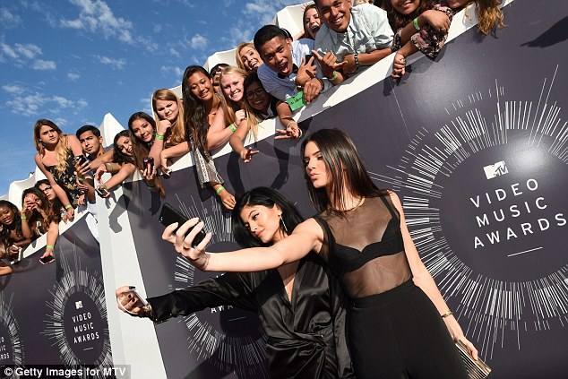 Time lapse: The texting incident caused an angry Twittering but some have speculated that it was camera time lapse; Kendall and Kylie made good use of their phones on the red carpet before the show