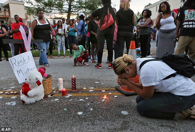 Meghan O'Donnell, 29, from St. Louis, prays at the spot where Michael Brown was killed on August 9