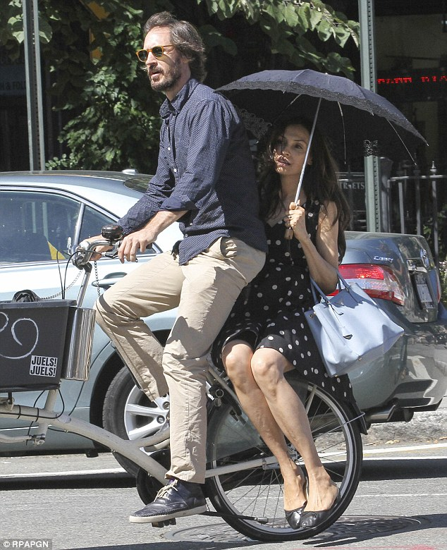 Romantic ride: Dutch actress Famke Janssen and her long-term love Cole Frates were seen heading home after lunch at West Village restaurant Bar Pitti on Thursday on the same bike