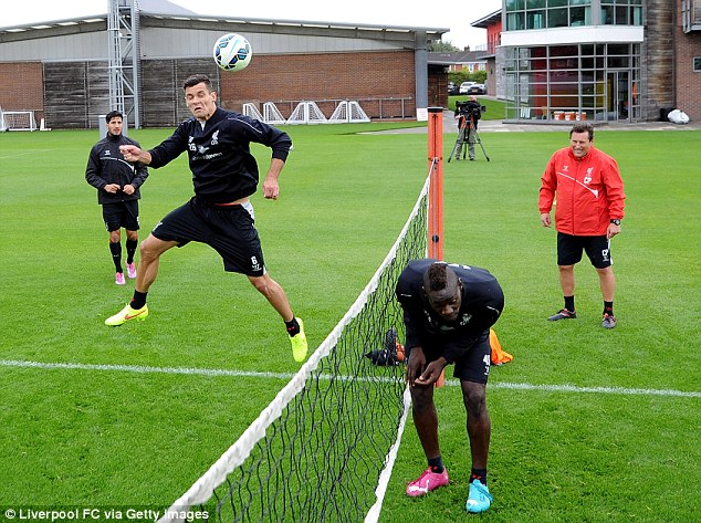 Up and down: Balotelli ducks as Dejan Lovren rises for a header on the other side of the net in training