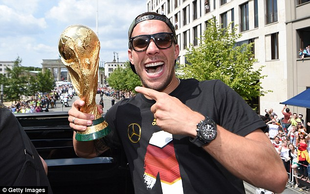 Prize guy: Arsenal's Germany star Lukas Podolski was all smiles after getting his hands on the World Cup