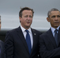 U.S. President Barack Obama, right, points as he stands alongside British Prime Minister David Cameron, centre, and NATO Secretary General Anders Fogh Rasmussen during a flypast at the NATO summit at the Celtic Manor Resort in Newport, Wales on Friday, Sept. 5, 2014. (AP Photo/Jon Super)