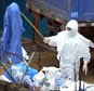 A worker in a Personal Protection Equipment suit (PPE) uses a stick to move garbage inside the high-risk quarantined zone of the John Fitzgerald Kennedy hospital in the Liberian capital Monrovia on September 5, 2014. Health experts were on September 5 debating a unproven drugs they hope will turn the lethal tide of Ebola, amid growing demands for more resources to go to frontline crisis care in some of the world's poorest states. The European Union announced 140 million euros ($183 million) in funds to fight the deadly Ebola virus in West Africa, a sharp increase over its previous pledge as the outbreak worsens. AFP PHOTO / DOMINIQUE FAGETDOMINIQUE FAGET/AFP/Getty Images
