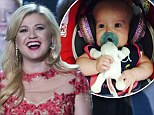 'Her first concert!': Kelly Clarkson takes three-month-old baby River Rose to Garth Brooks show... and decks her out in bejeweled headphones