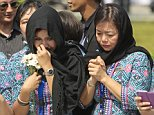 Malaysia Airlines crew members react as hearses carrying victims' bodies of the ill-fated Malaysia Airlines Flight MH17 leaving Bunga Raya Complex at Kuala Lumpur International Airport in Sepang, Malaysia, Friday, Aug. 22, 2014. The bodies and ashes of 20 Malaysians killed when Malaysia Airlines Flight 17 was shot down over Ukraine in July have arrived in Kuala Lumpur, the first repatriation of victims from the flight to the country. (AP Photo/Lai Seng Sin)