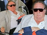 Bonjour Hollywood! Gerard Depardieu sparks up a cigarette as he is pushed through Los Angeles airport in a wheelchair