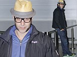 Funnyman Sacha Baron Cohen goes incognito as he catches a flight out of town... after staging fake arrest in South Africa
