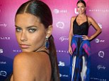 Adriana Lima shows off her model figure in black top and patterned maxi skirt as she leads stars attending Us Weekly party