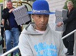 Pharrell Williams needs TWO assistants to carry his large collection of hat boxes as he continues European tour