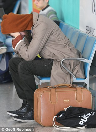 This man had his head in his hands at Stansted Airport in Essex