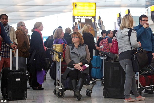 Travel hell: Passengers queue at the flight check-in desk to re-book tickets at London Heathrow Airport Terminal Five after a 'technical problem' at the National Air Traffic Services control centre caused long delays