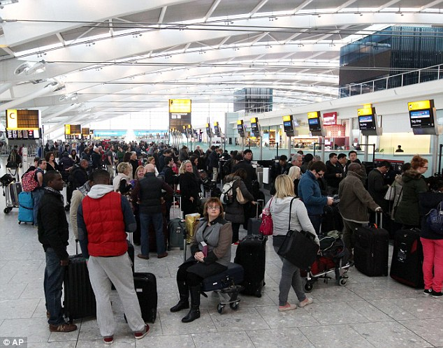Waiting game: Passengers queue at the flight check-in desk at London Heathrow Airport Terminal Five
