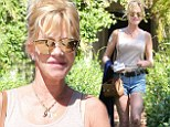 Melanie Griffith shows off long legs in shorts as she conceals Antonio tattoo with white patch
