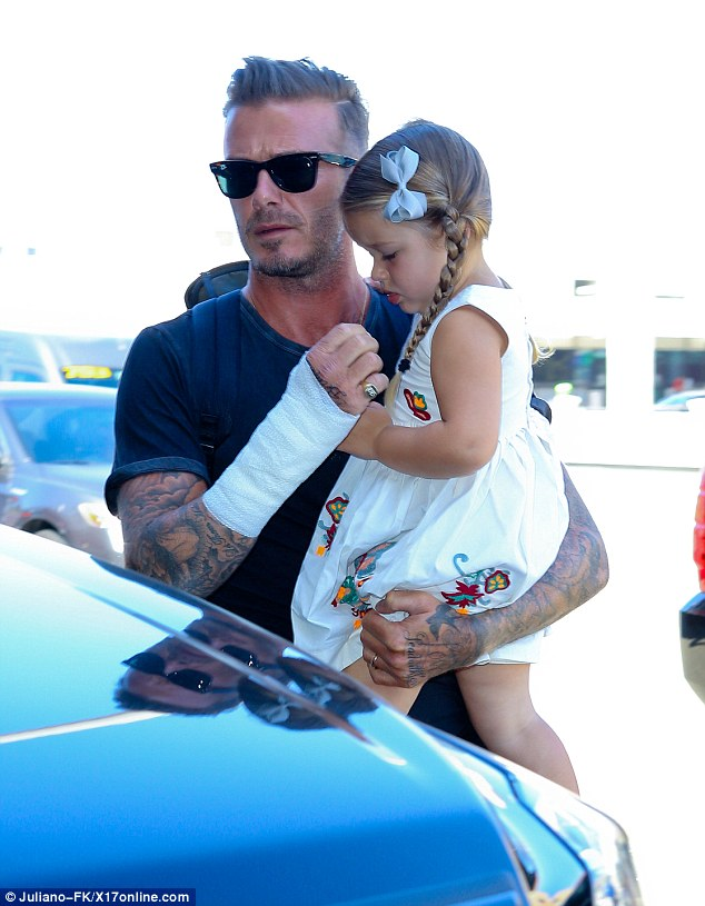 Precious cargo: David Beckham brandished a bandaged arm as he carried his daughter Harper to a departing flight at LAX on Friday