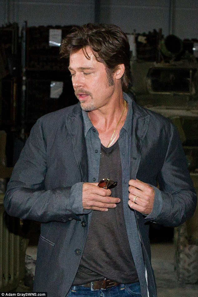 Done deal: Brad Pitt was more than happy to put his new wedding band on display as he attended a photocall in London on Thursday for his new film, Fury
