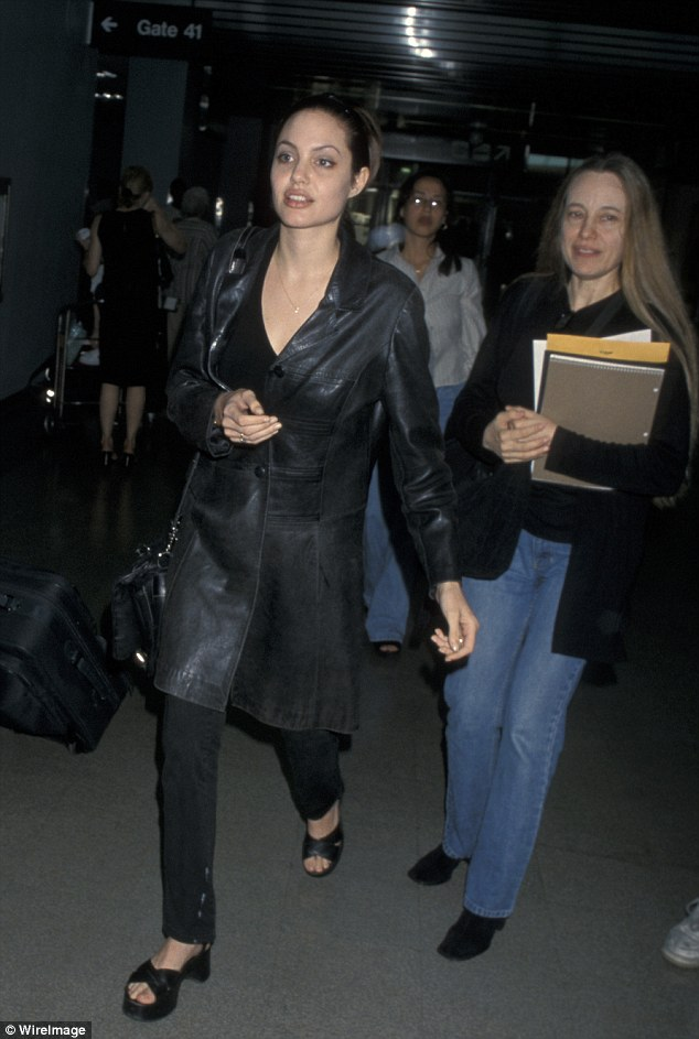 By her side: Friends have told how Angelina promised her mother she would marry in France. The pair are pictured together at Los Angeles airport in 1998