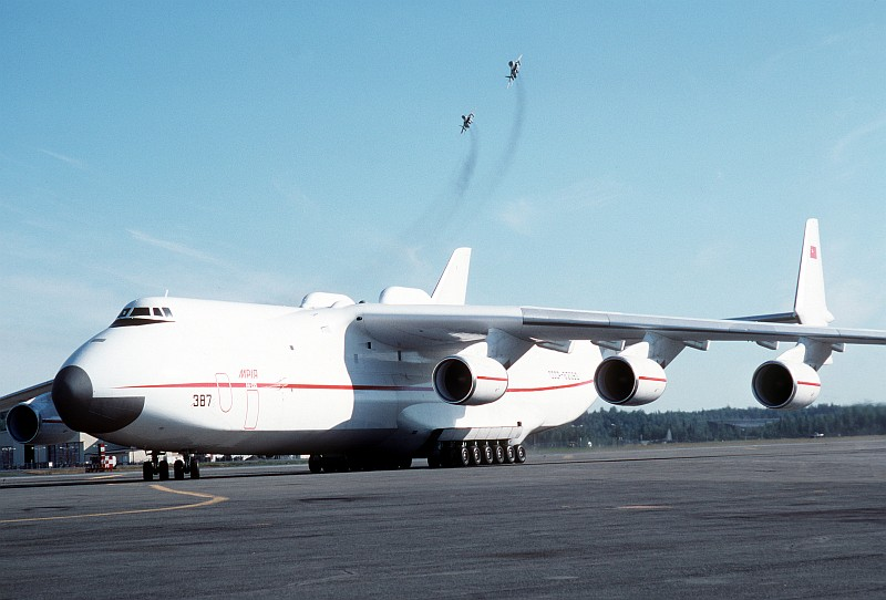 3. A Soviet An-225 Mriya Heavy Transport Aircraft Parked On the Flight Line As Two Fighter Jets Fly Overhead, August 1989, Elmendorf Air Force Base, State of Alaska, USA. Photo Credit: SSgt. Kevin L. Bishop, United States Air Force (USAF, http://www.af.mil); Defense Visual Information Center (DVIC, http://www.DoDMedia.osd.mil, DFST9005764) and United States Air Force (USAF, http://www.af.mil), United States Department of Defense (DoD, http://www.DefenseLink.mil or http://www.dod.gov), Government of the United States of America (USA).
