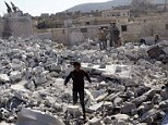 Residents inspect damaged buildings in what activists say was a U.S. strike, in Kfredrian, Idlib province