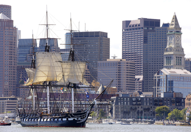 """The U.S.S. Constitution, or """"Old Ironsides,"""" the U.S. Navy's  oldest commissioned ship that is still afloat, is towed through Boston Harbor past the financia..."""