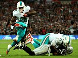 LONDON, ENGLAND - SEPTEMBER 28:  Lamar Miller #26 of the Miami Dolphins scores his team's second touchdown on a nine yard rush during the NFL match between the Oakland Raiders and the Miami Dolphins at Wembley Stadium on September 28, 2014 in London, England.  (Photo by Ben Hoskins/Getty Images)