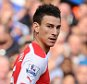 Laurent Koscielny of Arsenal appears to be expecting a straight red card as he walks away having fouled Eden Hazard of Chelsea for a penalty, but is awarded a yellow by referee Martin Atkinson