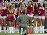 An airman purposes to an Arizona Cardinals cheerleader during the first half of an NFL football game against the Washington Redskins, Sunday, Oct. 12, 2014, in Glendale, Ariz.(AP Photo/Rick Scuteri)