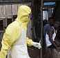 A health worker in protective equipment carries a sample taken from the body of someone who is suspected to have died from Ebola virus, near Rokupa Hospital, Freetown October 6, 2014. More than 4,000 people have died of the viral haemorrhagic fever in West Africa, mostly in Liberia, neighbouring Sierra Leone and Guinea. Picture taken October 6, 2014. REUTERS/Christopher Black/WHO/Handout via Reuters (SIERRA LEONE - Tags: DISASTER HEALTH) ATTENTION EDITORS - THIS PICTURE WAS PROVIDED BY A THIRD PARTY. REUTERS IS UNABLE TO INDEPENDENTLY VERIFY THE AUTHENTICITY, CONTENT, LOCATION OR DATE OF THIS IMAGE. FOR EDITORIAL USE ONLY. NOT FOR SALE FOR MARKETING OR ADVERTISING CAMPAIGNS. THIS PICTURE IS DISTRIBUTED EXACTLY AS RECEIVED BY REUTERS, AS A SERVICE TO CLIENTS