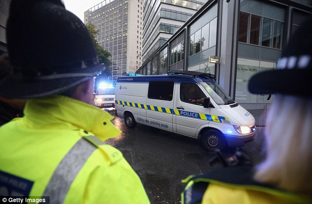 Driven: Police officers stand guard as Dale Cregan arrives in an armed convoy to face charges of murder and attempted murder