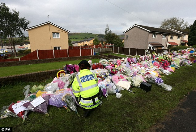 Moving: A police officer looks at flowers left at the scene of the shooting of PCs Fiona Bone and Nicola Hughes, in Hattersley, Greater Manchester