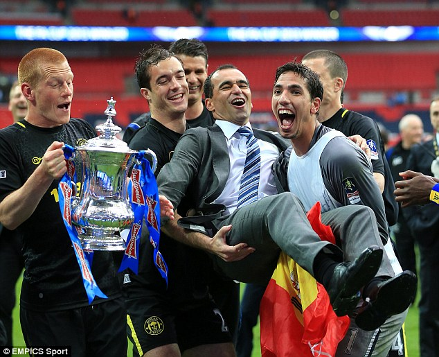 Pure delight: Watson cradles the FA Cup as Wigan boss Roberto Martinez is grabbed by his players