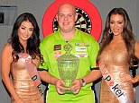 World No1 Michael Van Gerwen poses with the World Grand Prix title after beating James Wade 5-3
