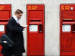A pedestrian passes royal mail post-boxes in London, Britain, 25 March 2014.   Royal Mail annouced it is planning to axe 1,600 jobs within the scope of its cost-saving plans.    EPA/ANDY RAIN. epa04140247