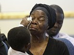 Garteh Korkoryah, mother of Thomas Eric Duncan, has her tears wiped by her great-grandson Josephus Weeks III at a memorial service for her son, Saturday, Oct. 18, 2014, in Salisbury, N.C. Duncan died of Ebola in Dallas on Oct. 8. (AP Photo/Nell Redmond)