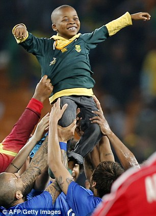 Lift him up: The boy looks delighted as Brazil players hold him over their heads