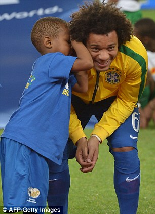 Cheeky chappy: Marcelo shares a joke with a young fan before the game
